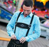 Funny bavarian man checking his lederhosen trousers