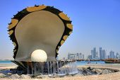 Monument symbolizing an oyster with skyline of Doha city in the background