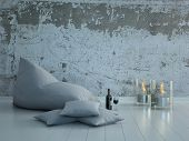White beanbag with pillows against concrete wall with candles