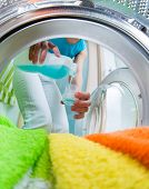 householder woman using conditioner for  washing machine