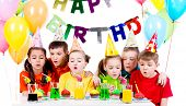 Group of kids in colorful shirts blowing candles at the birthday party - isolated on a white.