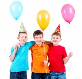 Portrait of three little boys with bright balloons and party hat - isolated on a white.