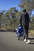 Dad Jogging With Baby Stroller On A Country Road