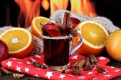 Fragrant mulled wine in glass on napkin on fire background
