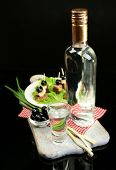 Composition with bottle of vodka, snacks with salted fish, green onion and glass on wooden board, is