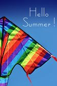 Hello Summer Sample Text With Bright Colorful Kite Flying High Over Blue Sky.