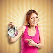 Happy Redhead Girl Holding A Clock Over Ocher Background