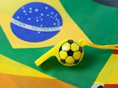 football shape whistle on brazil flag background.