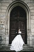 Mysterious woman in Victorian dress with old doors