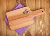 Cutting board over kitchen towel on wooden table background
