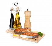 Grilled salmon with lemon and herbs on cutting board. Isolated on white background