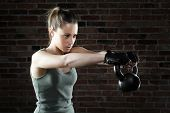 Young Fit Woman Lifting Kettle Bell