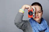 Portrait of a young woman with red retro camera wearing striped top and scarf on grey studio backgro