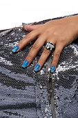 closeup of the woman's hand wearing luxury ring, blue gradient nail art manicure on silver sequin ma