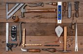High angle shot of an assortment of contractors well used tools. Horizontal format on a rustic wood background, with a bland space in the middle of the tool arrangement.