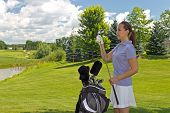 image of ladies golf  - Attractive woman selects her golf club from her golf bag - JPG