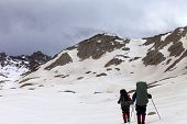 Two Hikers On Snowy Plateau Before Storm