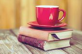 Books and a coffee cup on a wooden table