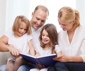 family, child and home concept - smiling family and two little girls with book at home