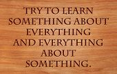 Try to learn something about everything and everything about something - quote on wooden red oak bac
