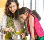stock photo of sari  - Asian family cooking food together at home - JPG