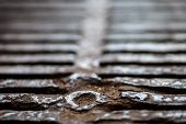 stock photo of metal grate  - Closeup of the metal drain grate surface - JPG
