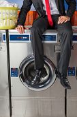 Low section of young businessman sitting on washing machine in laundry