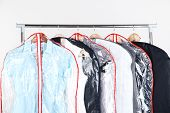 Office female clothes in cases for storing on hangers, on gray background
