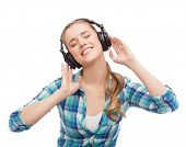 music and technology concept - smiling young woman listening to music in headphones