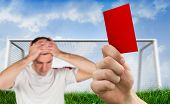 Composite image of hand holding up red card to player against goalpost on grass under blue sky