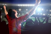 Cheering football fan in red jersey against large football stadium with lights
