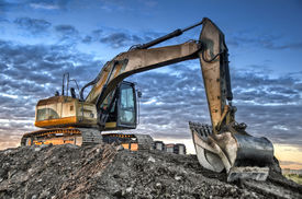 foto of power-shovel  - Excavator on construction site, and the sunrise in background. HDR effect.