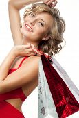 portrait of attractive  caucasian smiling woman blond isolated on white studio shot  toothy smile hair  looking at camera red dress shopping bags sale