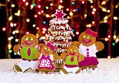 Gingerbread Cookie Family In Front Of Christmas Tree