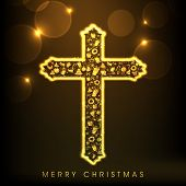 Shiny golden Christian Cross for Merry Christmas celebration on abstract brown background.