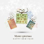 Floral decorated gift boxes with snowflakes on shiny background for Merry Christmas and Happy New Year celebrations.