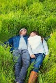 Romantic Young Couple in Love Outdoors. Lying in Grassy Field