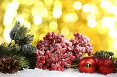 Christmas composition with baubles and fir-tree on snow on bright background