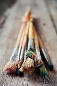 Old Artist Paintbrushes On Rustic Wooden Table