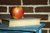 Apple with books on wooden stand on brick background