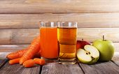 Carrot and apple juice and fresh carrots and apples on wooden table on wooden wall background