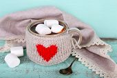 Cup of tasty hot cocoa, on wooden table, on color background