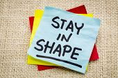 stay in shape reminder on a green sticky note against burlap canvas