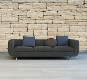 3D Rendering of Comfortable grey upholstered sofa with cushions standing on a grey parquet floor against a textured rough stone wall