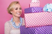 Woman with big beautiful smile holding colorful gift boxes. Soft colors. Christmas, birthday