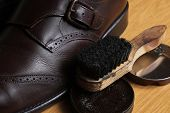 Brown leather classic Brogue shoes with polishing cream and brush on a table