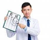 Optical doctor with eye chart and magnifying glasses
