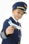 A young elementary boy playing commercial pilot in his blue and gold uniform and small commercial airplane.  On a white background.