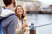 candid couple eating icecream on date having fun smiling