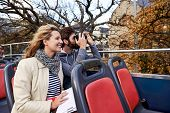 couple on open top tourist bus in city taking photos on vacation